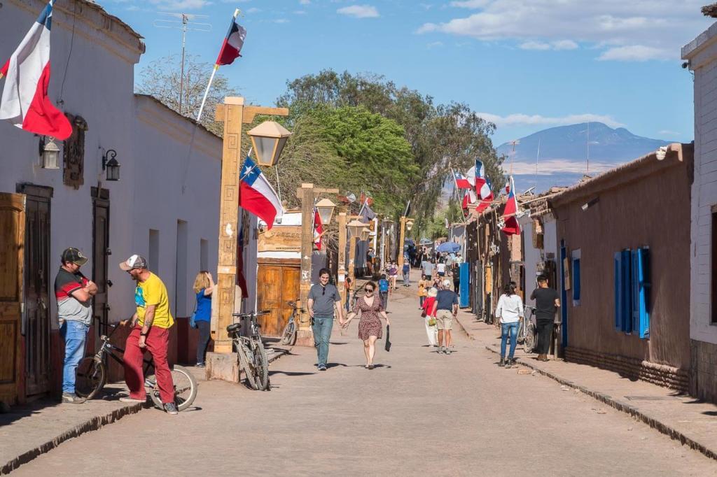 Deserto do Atacama Chile - Calle Caracoles é a rua mais movimentada de San Pedro de Atacama, com construções baixa, chão de terra pessoas circulam buscando restaurante, agências de passeios e hotéis