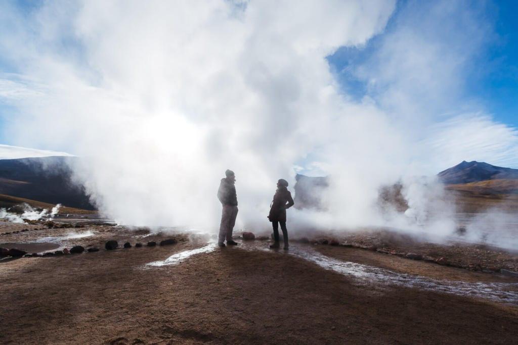 Deserto do Atacama Chile - Foto Caio e Adriana em meio a fumaça liberada pelo vapor dágua no clima frio da manhã no Geyser Del Tatio