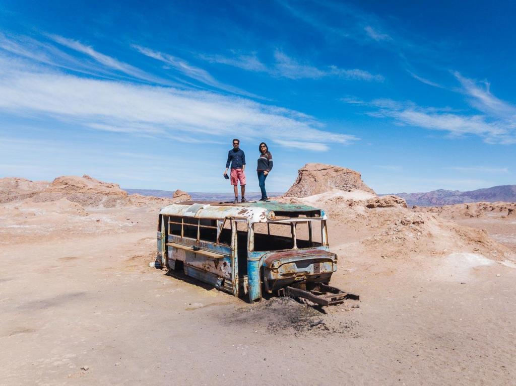 Deserto do Atacama Chile - imagem do ônibus abandonado no meio do deserto do Atacama com Caio e Adriana em pé em cima