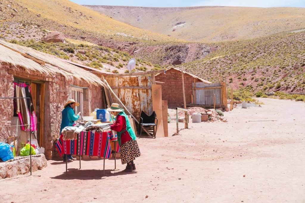Deserto do Atacama Chile - Duas moradoras de Povoado Machuca arrumam a mesa para expor e vender artesanato