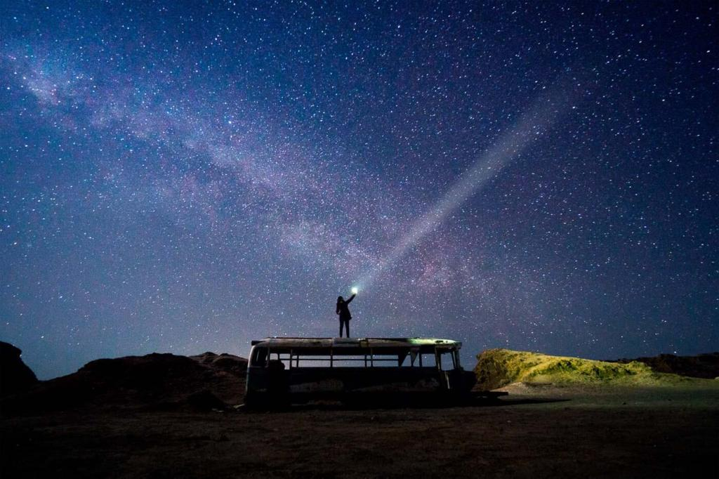 Fotografia da Adriana no tour astronomico em cima do onibus abandonado no Deserto do Atacama com a via Lactea ao fundo