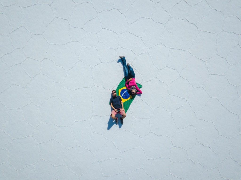 Salar de Uyuni - Foto do Caio e da Adriana deitados sobre uma bandeira do Brasil no meio do deserto de Sal