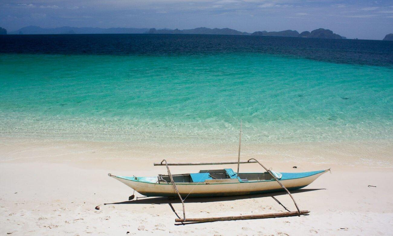 Foto de um barco filipino na água cristalina - Coron Filipinas