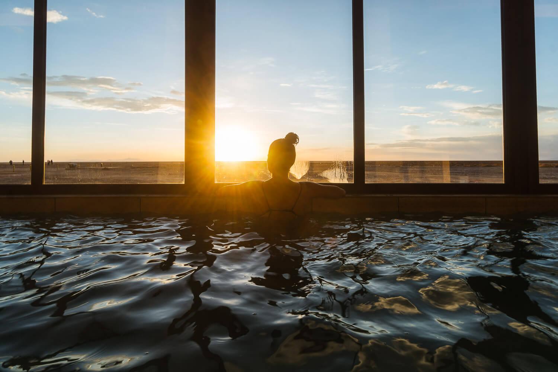 Foto da Dro observando o pôr do sol de dentro da piscina - hotel de sal no Uyuni
